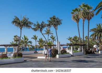 Tenerife, Canary islands - april 22, 2019: Tourists walking along the avenue of Colon in front of the Martianez swimming pools in the city of Puerto de la Cruz, north of the island