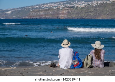 Tenerife, Canary islands - april 22, 2019: A couple of tourists contemplating the sea on the coast of Martianez in the city of Puerto de la Cruz, north of the island