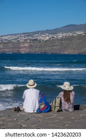 Tenerife, Canary islands - april 22, 2019: A couple of tourists contemplating the landscape from the coast of Martianez in the city of Puerto de la Cruz, north of the island