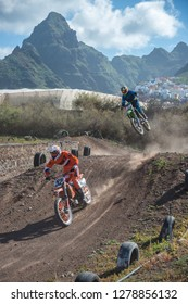 Tenerife, Canary islands - December 29, 2018: Image with motion blur of motocross bikes jumping on a training track on the Punta del Hidalgo coast, with landscape of mountains in the background
