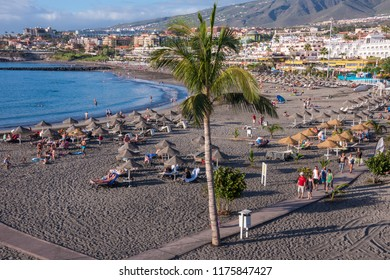 Tenerife, Canary islands - february 23, 2016: Walk with palm trees and Fanabe beach at sunset, on the south coast of the island