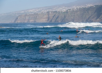 Tenerife, Canary islands - january 04, 2018: Surfers catching waves on the beach of Martianez, on the coast of the tourist city of Puerto de la Cruz, in the north of the island