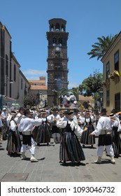 Tenerife, Canary islands - july 12, 2009: Folk group dancing through the streets of La Laguna during the pilgrimage of San Benito Abad, with the tower of the church of La Concepcion in the background