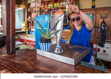 Tenerife, Canary islands - july 23, 2018: Young waitress serving a beer at a kiosk bar on the beach of La Jaquita in Medano, on the south coast of the island at sunset