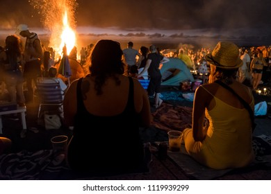 Tenerife, Canary islands - june 23, 2018: Backlight of two girls with their backs watching a bonfire burn, at the Jardin Beach of Puerto de la Cruz, on the night of San Juan