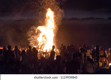 Tenerife, Canary islands - june 23, 2018: Silhouettes of people around a bonfire, at the Jardin Beach of Puerto de la Cruz, on the night of San Juan