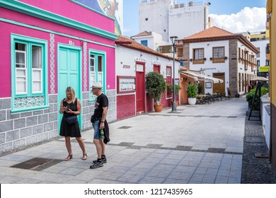 Tenerife, Canary islands - October 27, 2018: Couple of tourists consulting the mobile in a pedestrian street in La Ranilla, an old fishing district of the tourist city of Puerto de la Cruz