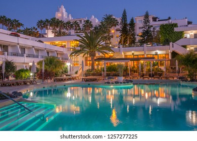 Tenerife, Canary islands - September 13, 2016: View of a pool and apartment buildings at dusk on the coast of Playa de las Americas, in the south of the island