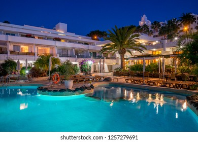 Tenerife, Canary islands - September 13, 2016: Pool, gardens and apartment buildings at dusk at Playa de las Americas, in the south of the island
