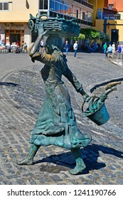 TENERIFE, CANARY ISLANDS, SPAIN - APRIL 03: Bronze sculpture of a fishmonger from sculptor Julio Neto  in Puerto de la Cruz, on April 03, 2018 in Tenerife, Spain