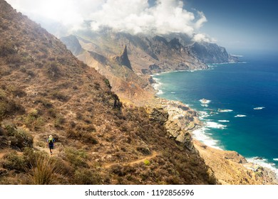 Tenerife, Canary Islands, Spain - September 30, 2018: man hiking through Anaga mountains with Roque de Las Animas rock formation in background, in Tenerife island.