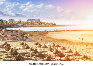 TENERIFE, SPAIN - JANUARY 14, 2013: Straw umbrellas and loungers on the Playa de Las Americas, Tenerife, Canary Islands, Spain