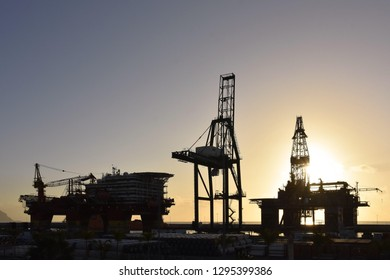 Tenerife, Spain - March 12, 2018: Cranes and oil rig platforms silhouetted against morning sun in the port of Santa Cruz de Tenerife Canary Islands Spain.
