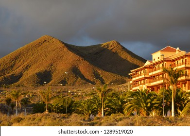 Tenerife, Spain - March 29, 2016: Modern hotel apartment building, dark rainy clouds forming over arid volcanic landscape of Los Cristianos, southwest of Tenerife Canary Islands Spain