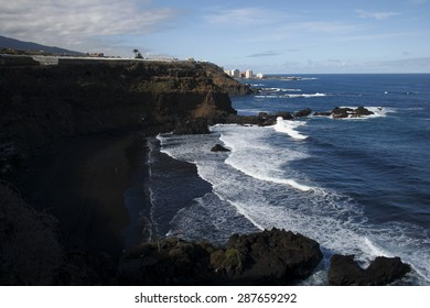 Tenerife,Black Sand Beach,natural beach near Puerto de la Cruz on the island of Tenerife, small cliffs of volcanic rock, Atlantic Ocean waters bathe the sand, white foam contrast with black sand