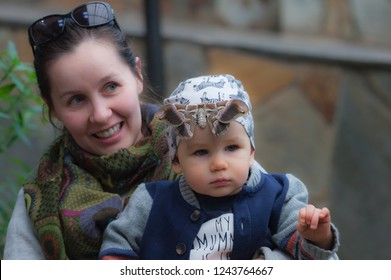 Tenerife/Spain - 02.11.2018: A nice photo pf a mother and son posing with a specimen of Indian eri silkmoth (Samia ricini) resting on the toddler's forehead