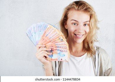 Tenge. A beautiful blonde girl in a white t-shirt smiles and holds in her hand a lot of Kazakh bills on a white background close-up.
