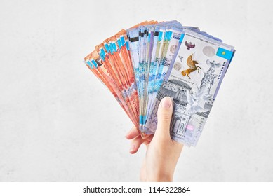 Tenge. The female hand holds many Kazakh bills on a white background close-up.