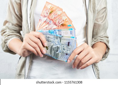 Tenge. A girl in a white t-shirt holding a lot of Kazakh bills close-up.