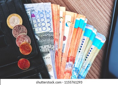 Tenge. Kazakh money in a black wallet on the background of the table close-up.