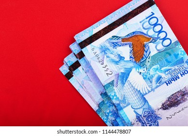 Tenge. Kazakh money. Pack of bills in the corner on a red background close-up.