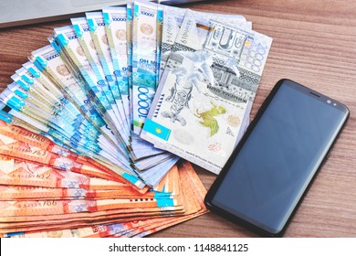 Tenge. A lot of Kazakh paper money and a mobile phone on the background of a brown table close-up.