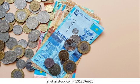 Tenge. Money. Kazakh coins and bills are on the beige table top view.