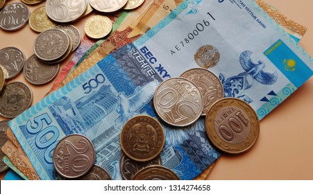 Tenge. Money. Kazakh coins and bills are on the beige table close-up.