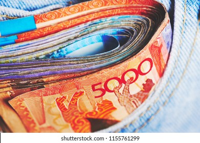 Tenge. A pack of Kazakh banknotes is in the pocket of jeans close-up.
