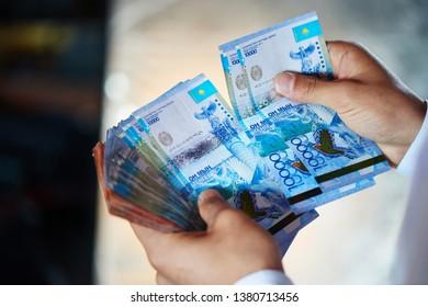Tenge paper. Hands of businessman in a shirt count Kazakh money close up.