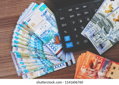 Tenge. Paper Kazakh money and calculator on the table close-up.