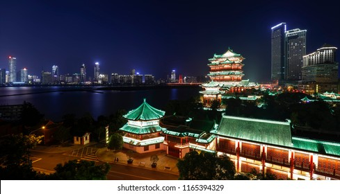 Tengwang Pavilion,Nanchang,traditional, ancient Chinese architecture, made of wood.Contrast with modern high-rise buildings.The night scenery of the cities along the Yangtze River.