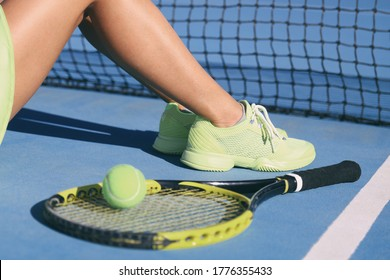 Tennis athlete player woman legs and feet wearing tennis shoes trainers. Fashion yellow activewear outfit on blue outdoor hard court. Closeup of legs and feet, racket and ball.