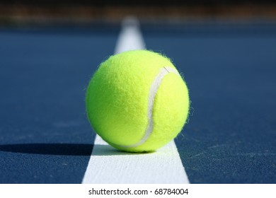 Tennis Ball cetnered on the court line