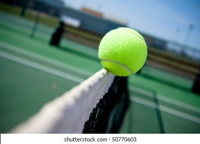 A tennis ball clips the top of the net and goes over to the other side.