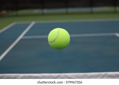 Tennis Ball Flying in Mid Air over Net on Blue Green Court