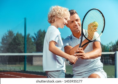 Tennis ball. Handsome athletic father showing his cute curly son tennis ball before playing