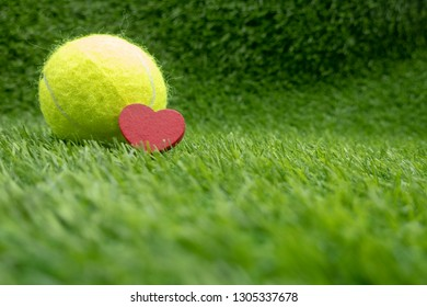 Tennis ball with heart shape on green grass for tennis player with love on Valentine's Day