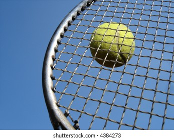 Tennis ball hitting racket against blue sky.