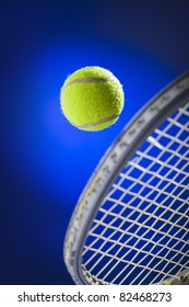 Tennis ball just about to be hit from the tennis racket  on blue background