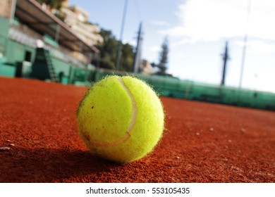 Tennis ball laying on the clay.
