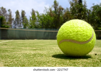 A tennis ball laying on a court. Summer. Sunny day.