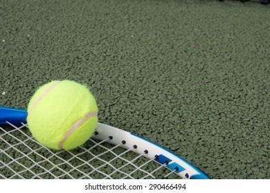 tennis ball lying on racket on tennis court