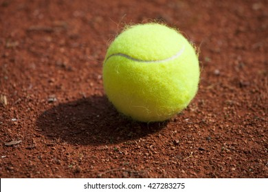 tennis ball on a bed of red slag