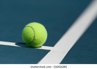 Tennis ball on blue hard court inside of line