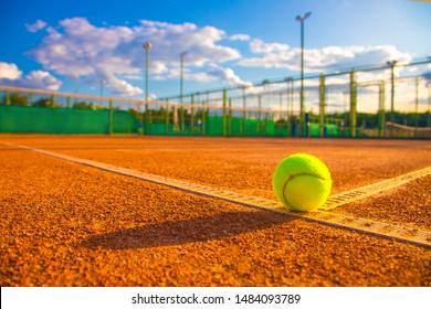 Tennis ball on a clay court.