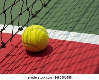 Tennis ball on court with casted net shadow