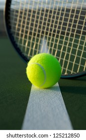 Tennis Ball on the Court Line with the Racket Beyond