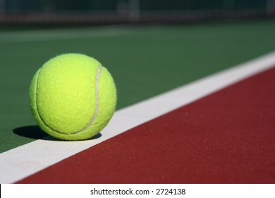 Tennis ball on the court line diagonal