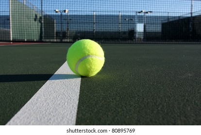Tennis Ball on the Court with net in the background